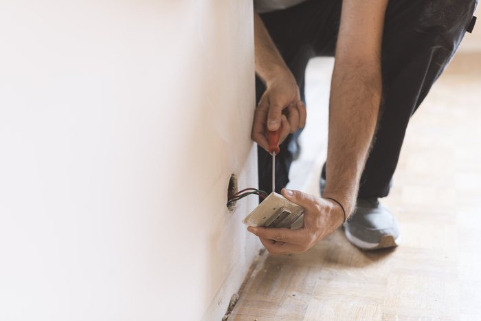 professional electrician installing sockets at home