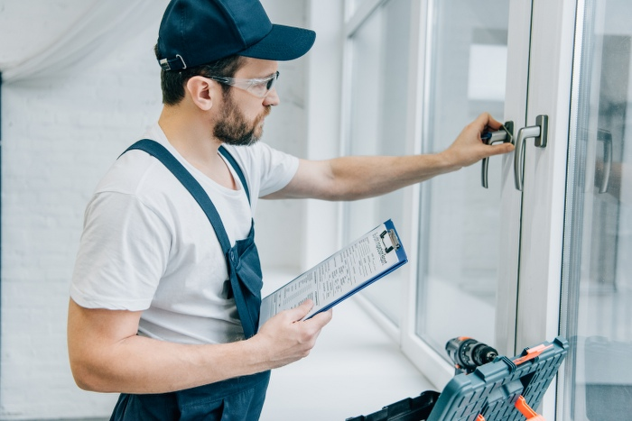handyman checking window handle