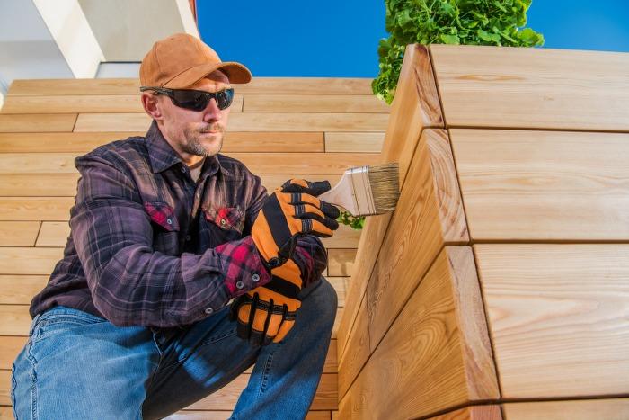 man using brush on wooden plank