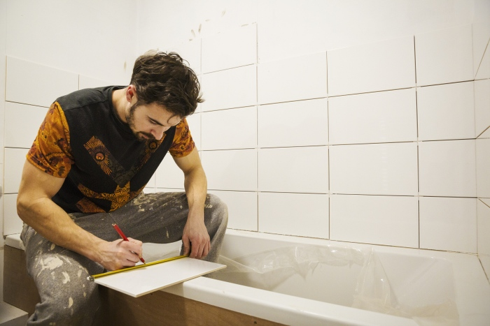 tiler working in bathroom